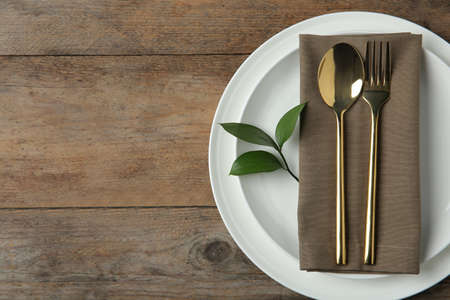Beautiful table setting on wooden background, flat lay. Space for text