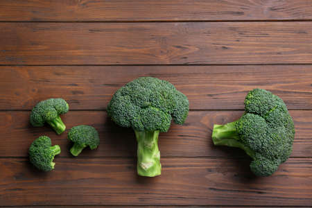 Flat lay composition of fresh green broccoli on wooden table, space for text