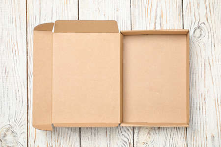 Open cardboard box on white wooden background, top view Stock Photo