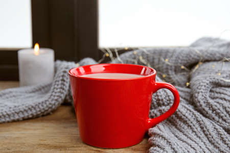 Cup of hot cocoa and sweater on window sill. Winter drink