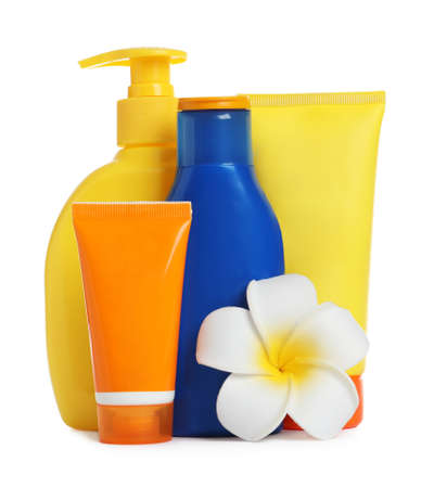 Composition with sun protection cosmetic products and flower on white background