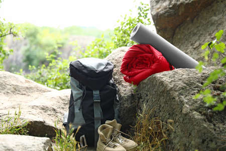 Rolled sleeping bag, mat, boots and backpack outdoors Фото со стока