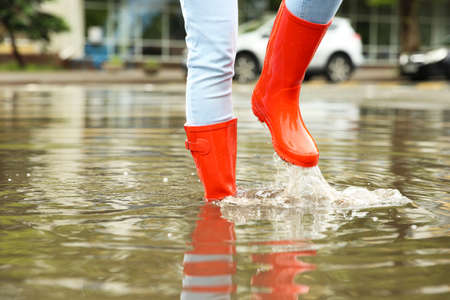 Mujer con botas de goma roja en charco, primer plano. Clima lluvioso Foto de archivo