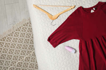 Female roll-on deodorant and clothes on bed, top view. Space for text