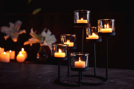 Holder with burning candles on table in darkness, space for text. Funeral symbol