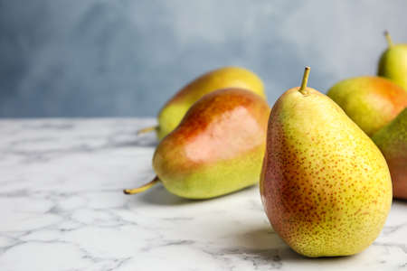 Ripe juicy pears on marble table against blue background. Space for text