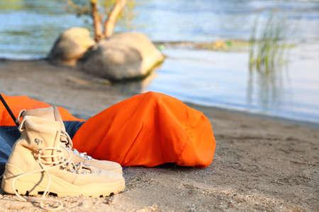 Sleeping bag and boots on beach near lake