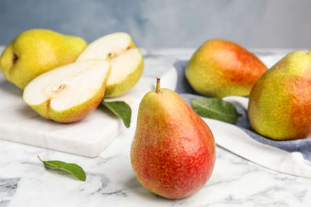 Ripe juicy pears on marble table against blue background