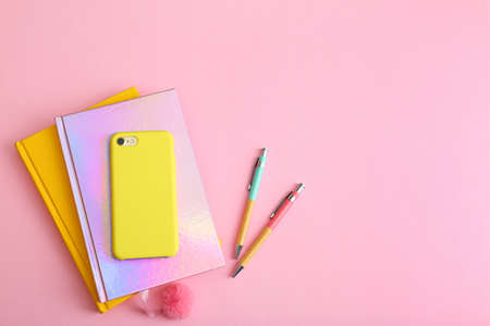 Smartphone, notebooks and pens on pink background, flat lay