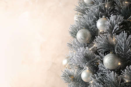 Beautiful Christmas tree with decor on light background. Space for text