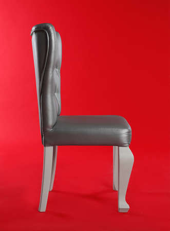 Stylish silver chair on red background. Element of interior design