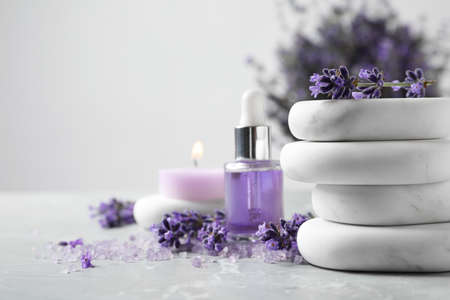 Spa stones, natural cosmetic oil and lavender flowers on grey table, space for text