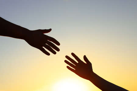 Man giving hand to woman outdoors at sunset, closeup. Help and support concept