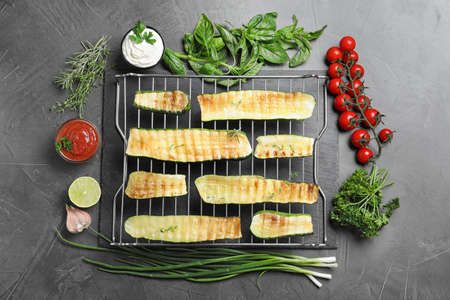 Flat lay composition with delicious grilled zucchini slices on grey table Stock fotó