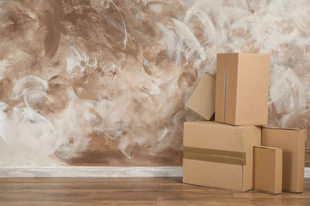 Pile of cardboard boxes near brown wall indoors. Space for text Stock Photo - 130132922