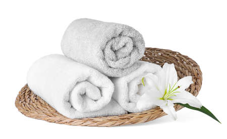 Wicker tray with towels and flower isolated on white. Spa treatment Фото со стока