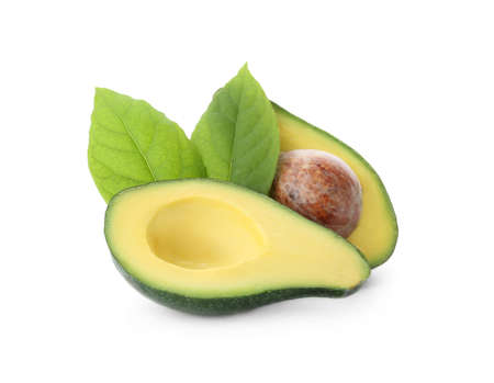 Halves of fresh ripe avocado and leaves on white background