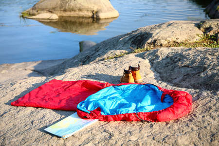 Sleeping bag, boots and map outdoors on sunny day Banco de Imagens - 130132926