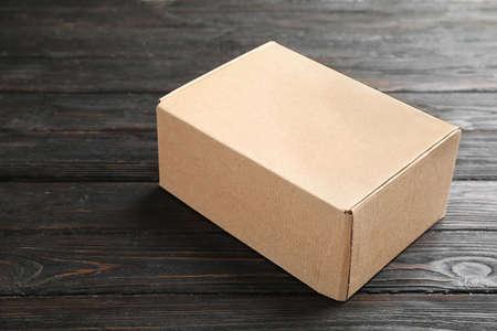 Closed cardboard box on dark wooden table Stock Photo