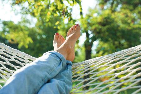 Young woman resting in comfortable hammock at green garden, closeup