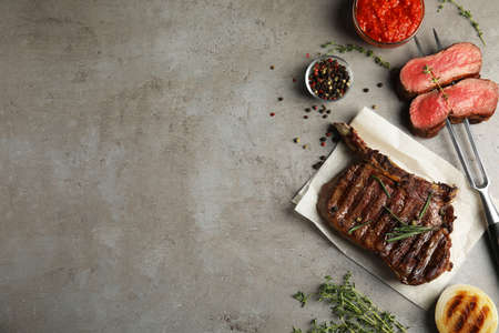 Flat lay composition with grilled meat steak on grey table. Space for text