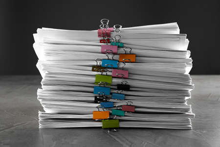 Stack of documents with binder clips on grey stone table