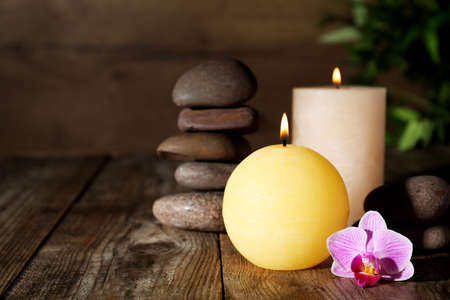 Composition with candles and spa stones on wooden table. Space for text