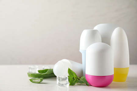 Roll-on deodorants, aloe and ice with mint on white wooden table, space for text Фото со стока