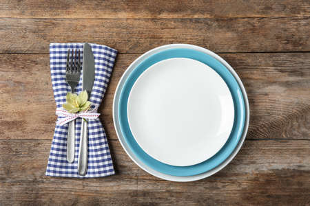 Beautiful table setting on wooden background, flat lay