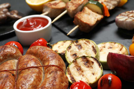 Barbecued meat and vegetables on grey table, closeup Stock Photo
