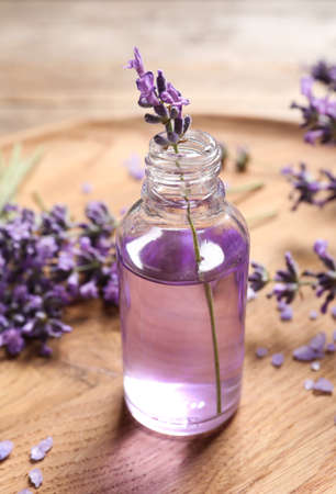 Glass bottle of natural cosmetic oil and lavender flowers on wooden plate