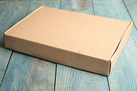 Closed cardboard box on light blue wooden table