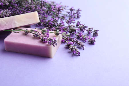 Hand made soap bars with lavender flowers on violet background, space for text