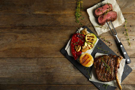 Flat lay composition with grilled meat on wooden table. Space for text Stock Photo