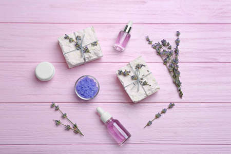 Flat lay composition with hand made soap bars and lavender flowers on pink wooden table