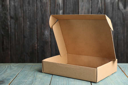 Cardboard box on light blue wooden table against dark background Stock Photo - 130133087