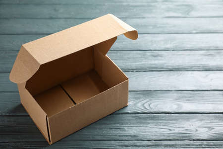 Open cardboard box on dark wooden table. Space for text