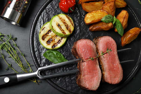 Flat lay composition with slices of grilled meat on black table