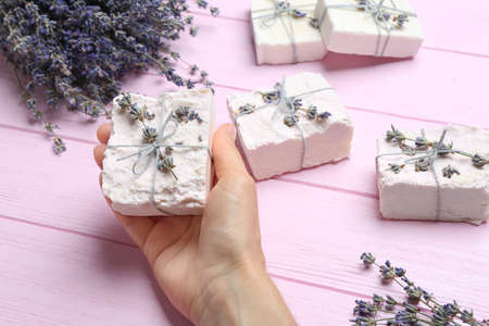 Woman holding hand made soap bar with lavender flowers on pink wooden background, closeup Stock Photo