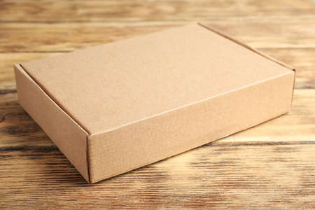Closed cardboard box on brown wooden table Stock Photo - 130133125