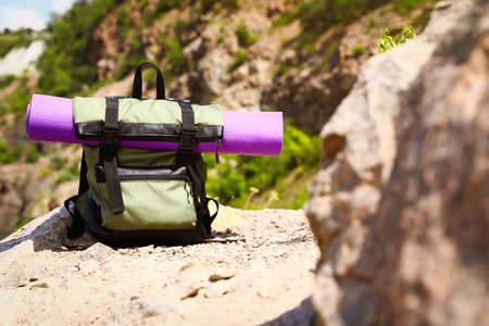 Backpack with sleeping mat outdoors on sunny day