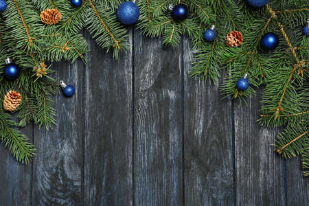Fir tree branches with Christmas decoration on dark wooden background, flat lay. Space for text Standard-Bild - 130133141