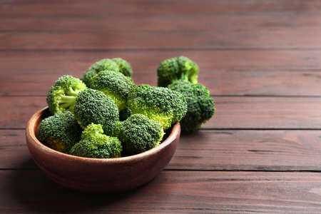 Bowl of fresh green broccoli on wooden table, space for text Zdjęcie Seryjne