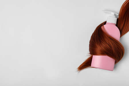 Shampoo bottle wrapped in lock of hair on white background, top view. Natural cosmetic products
