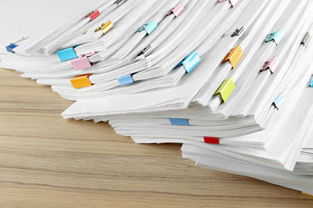 Stack of documents with binder clips on wooden table, closeup view Stock Photo