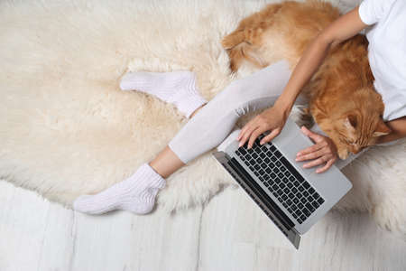 Woman with cute red cat and laptop on fur carpet, top view. Space for text