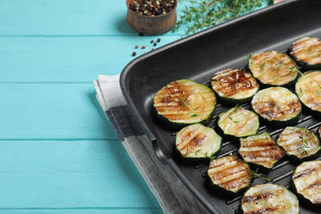 Grill pan of delicious zucchini slices on blue wooden table, closeup. Space for text
