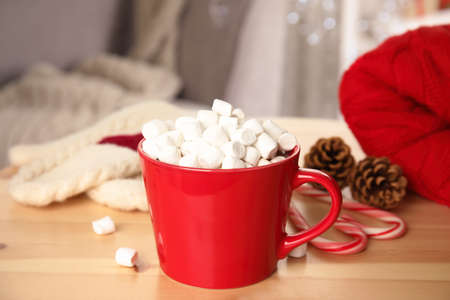 Cup of hot cocoa with marshmallows on wooden table indoors. Winter drink Stok Fotoğraf