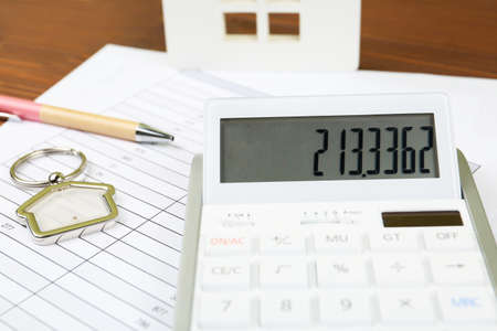Calculator, house shaped trinket, pen and documents on table. Real estate agents workplace