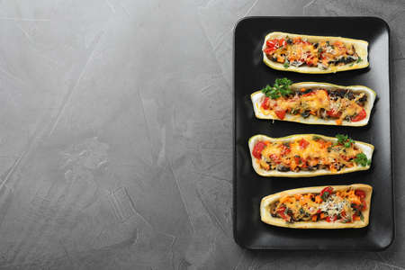 Delicious stuffed zucchini on grey table, top view. Space for text Stock fotó